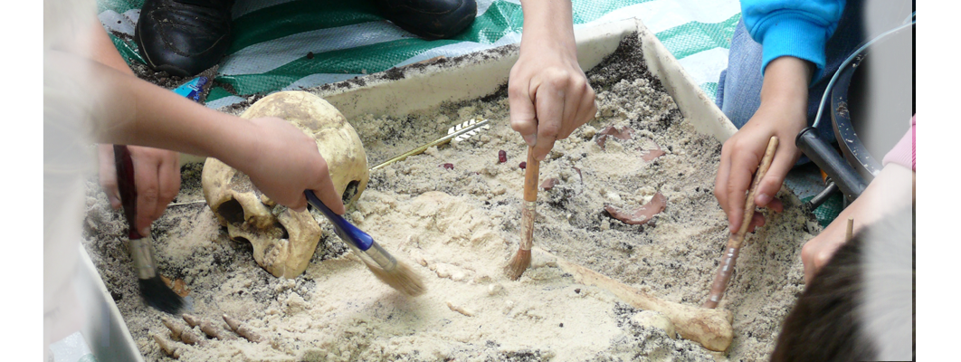 Children learning to excavate a fake skeleton